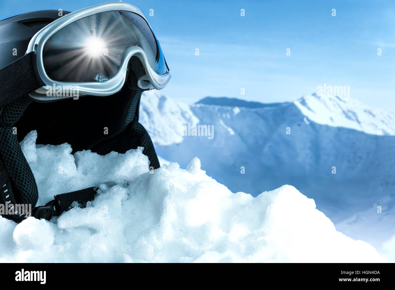 Helmet and ski goggles on snow with a blue sky and mountains - Stock Image