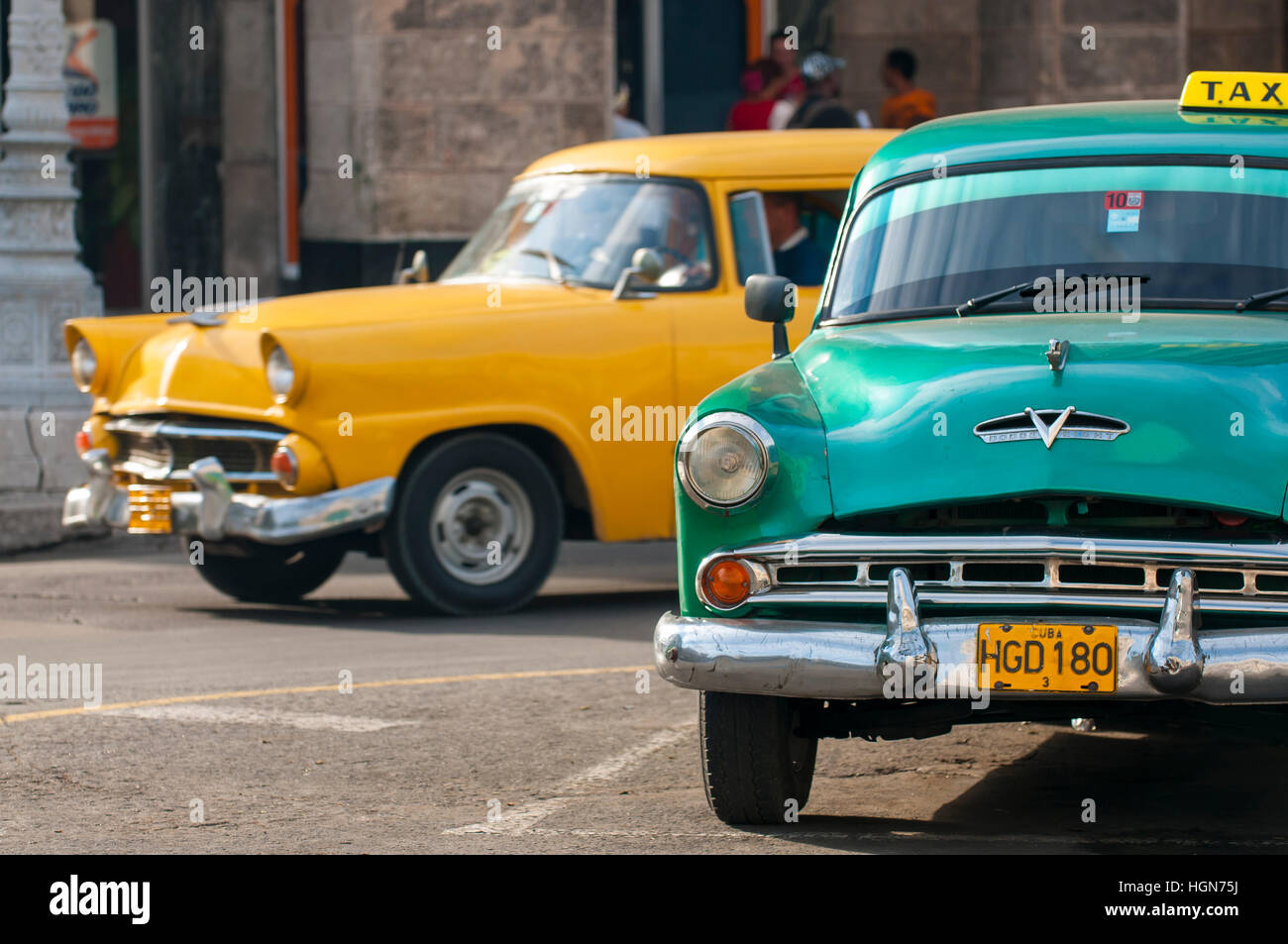 HAVANA - JUNE 13, 2011: Classic American taxi cars, symbols of the historical city, pass on a street in the Centro - Stock Image