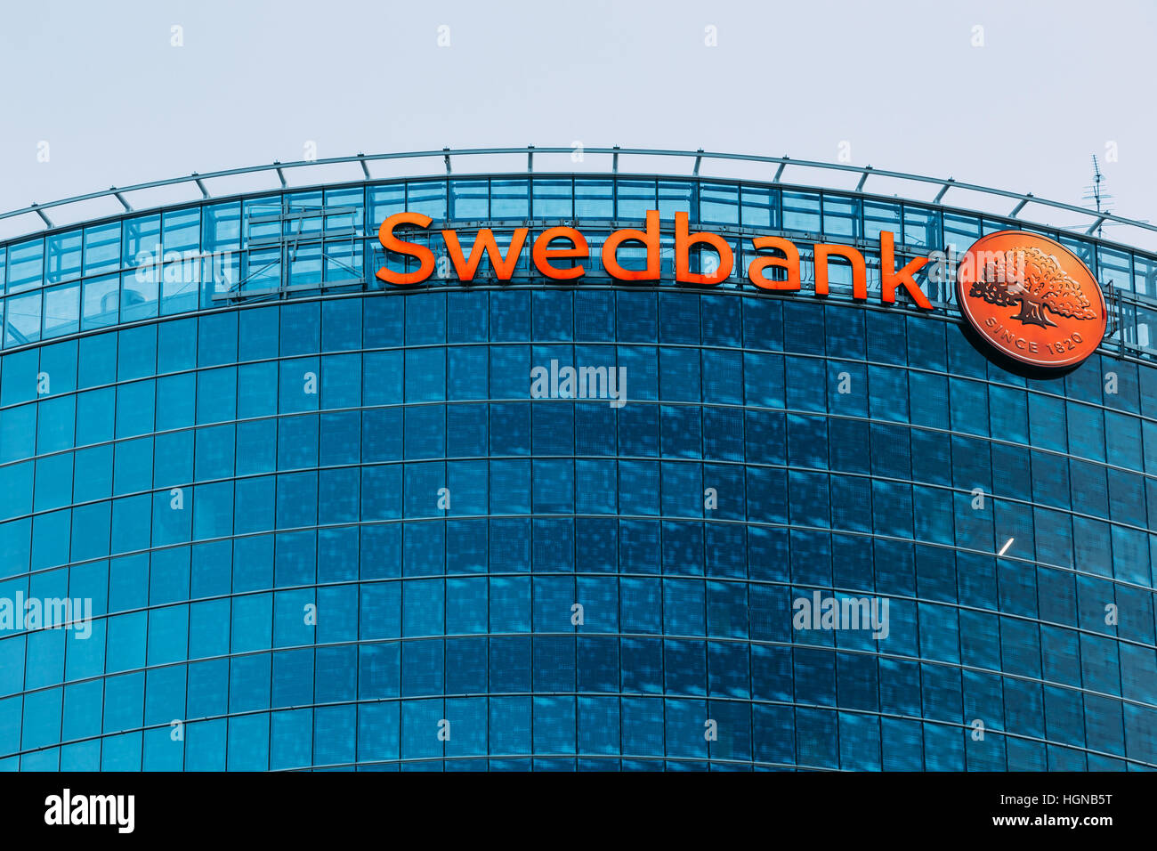 Riga, Latvia - June 30, 2016: Close View Of Blue Glass Building Facade Of Headquarter Of Swedbank With Red Signboard - Stock Image