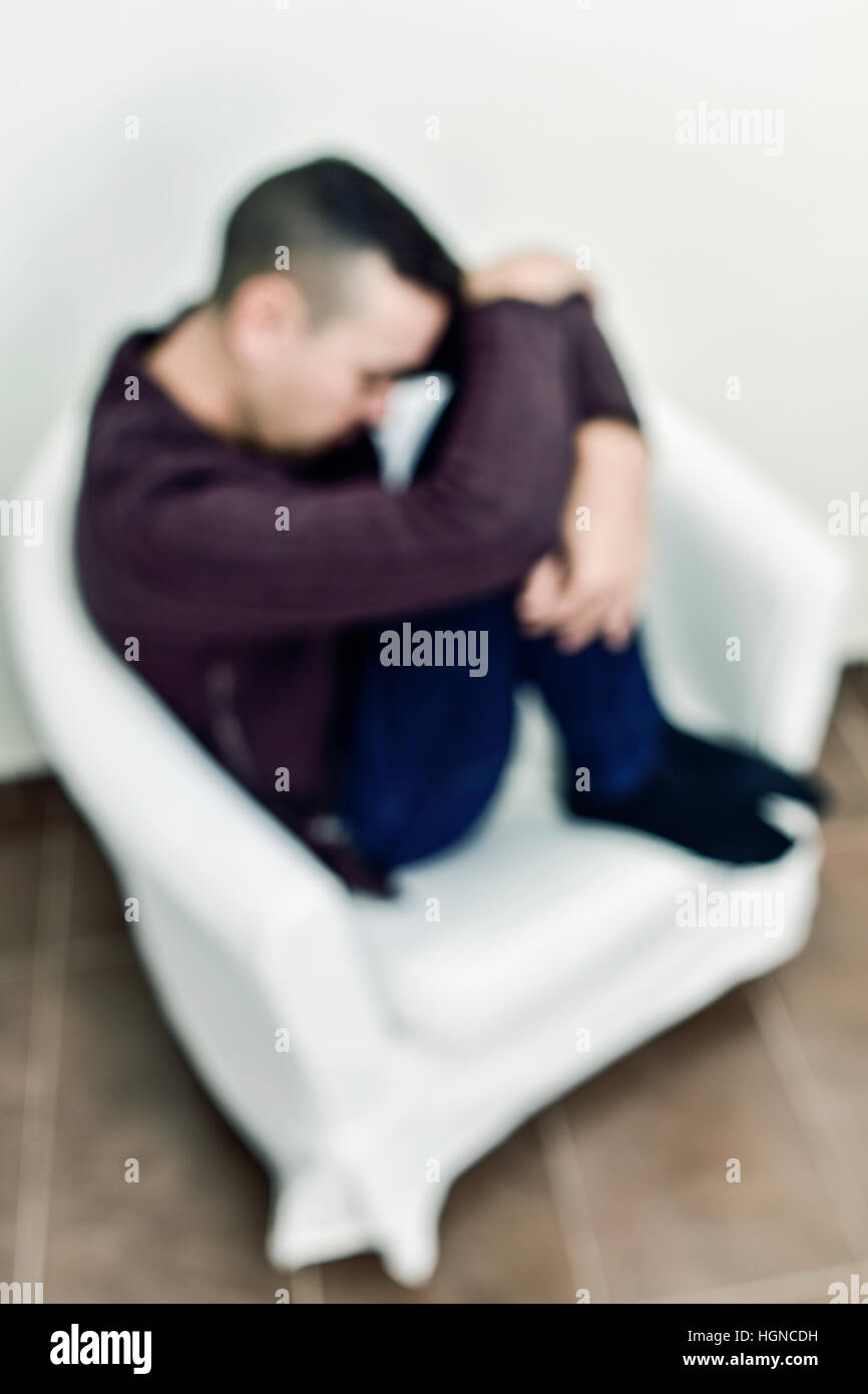 closeup of a blurred young caucasian man curled up in a white armchair - Stock Image