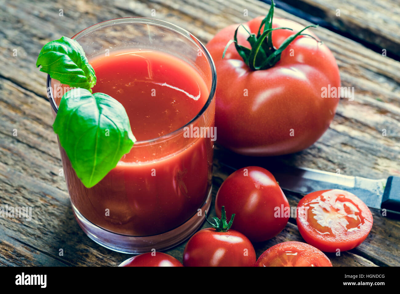 Glass of tomato juice and a few tmatos on wooden table - Stock Image