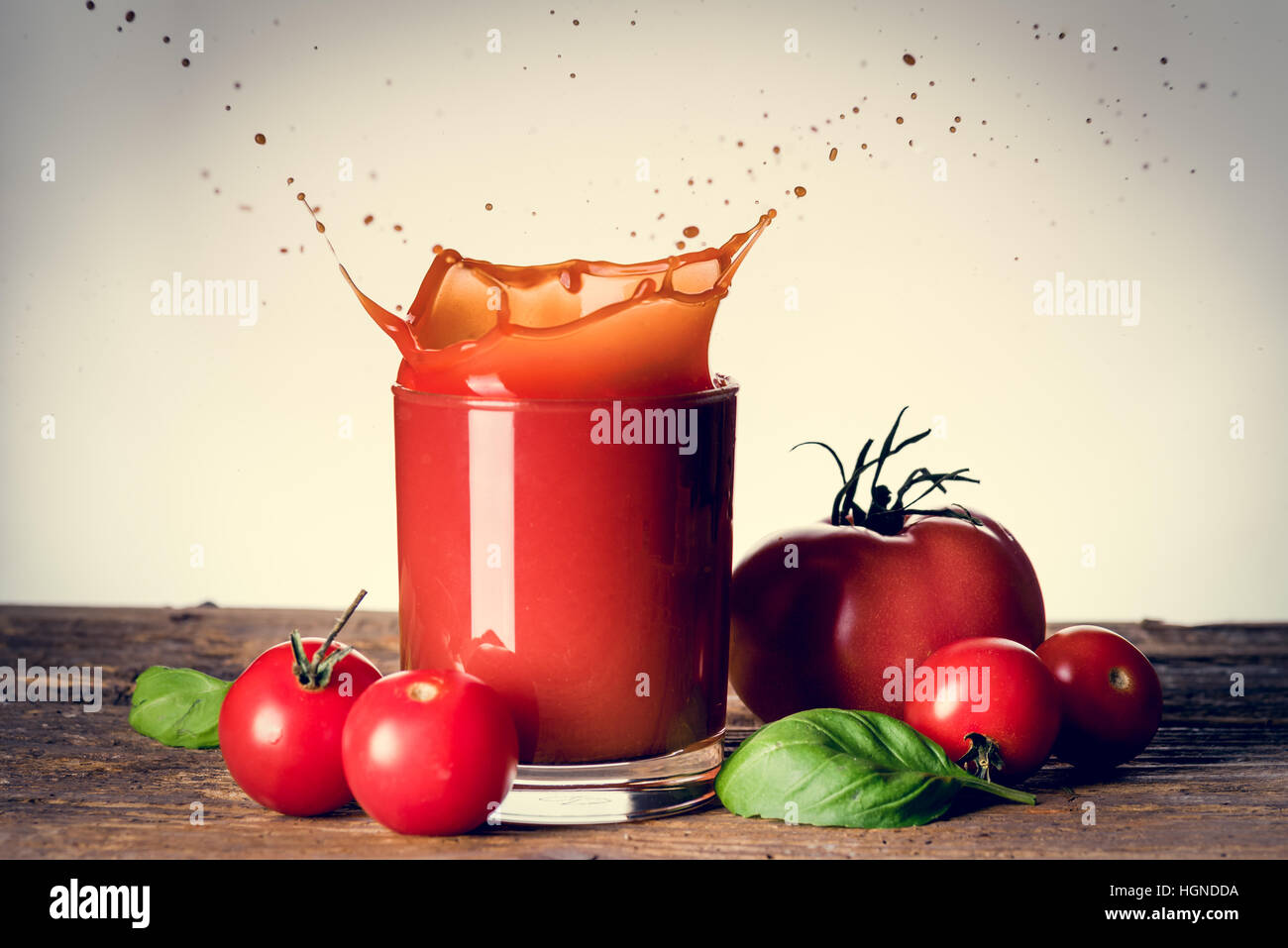 Tomato juice splashing over the glass on the wooden table - Stock Image