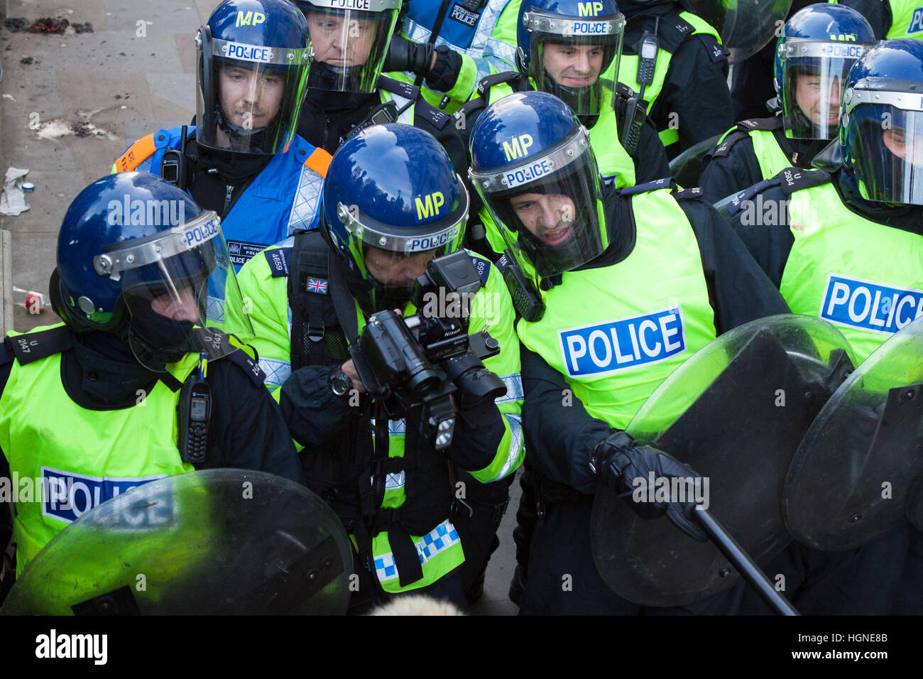 A Metropolitan (Met) Police officer points to a subject for a FIT photographer at a protest demonstration in London - Stock Image
