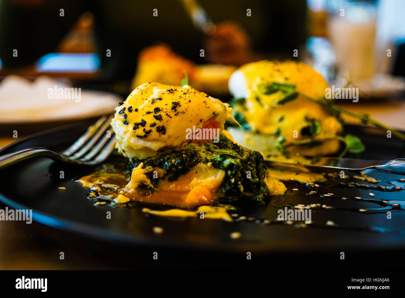 Eggs Florentine close up on a black plate with a fork also in shot - Stock Image