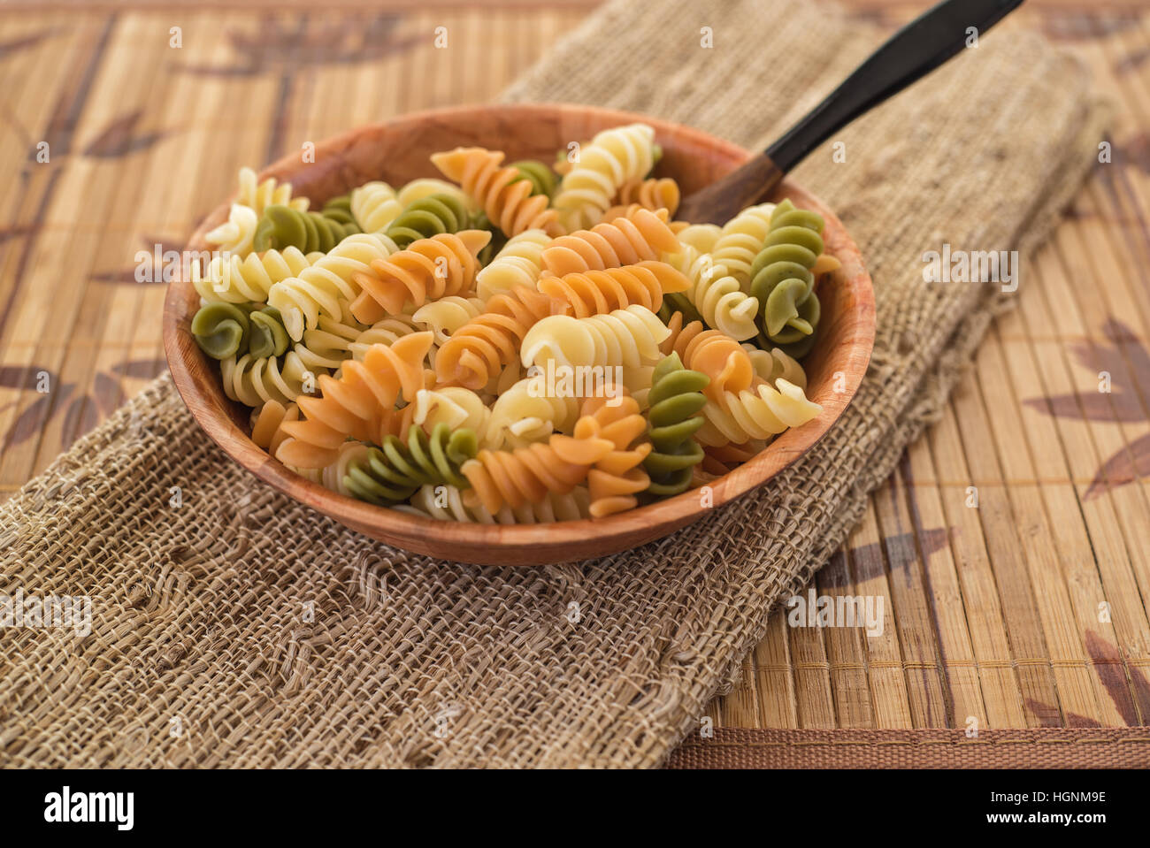 Close up of a wooden bowl with pasta on a burlap table cloth - Stock Image