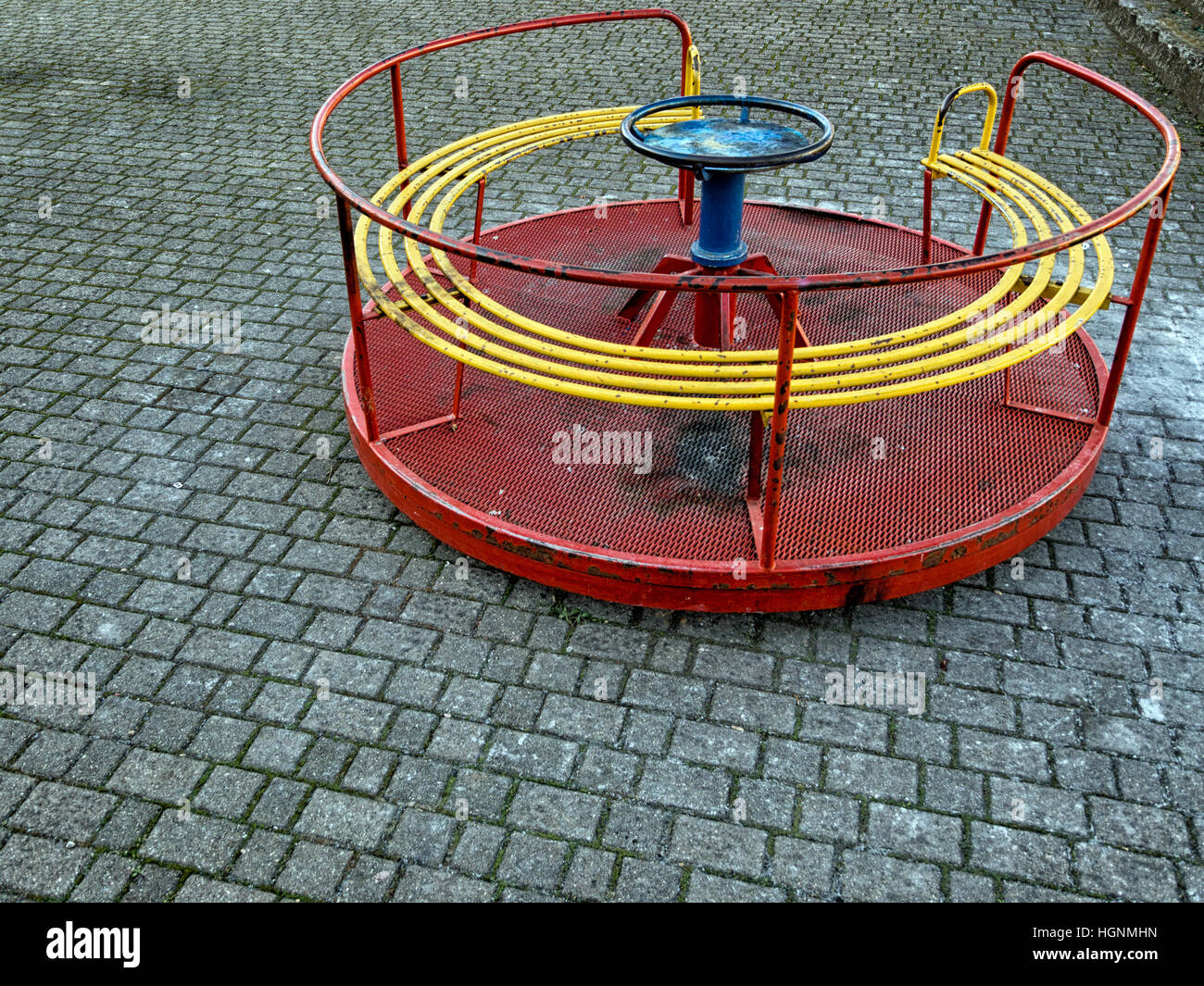 Empty playground, old roundabout. Urban environment, no children. - Stock Image