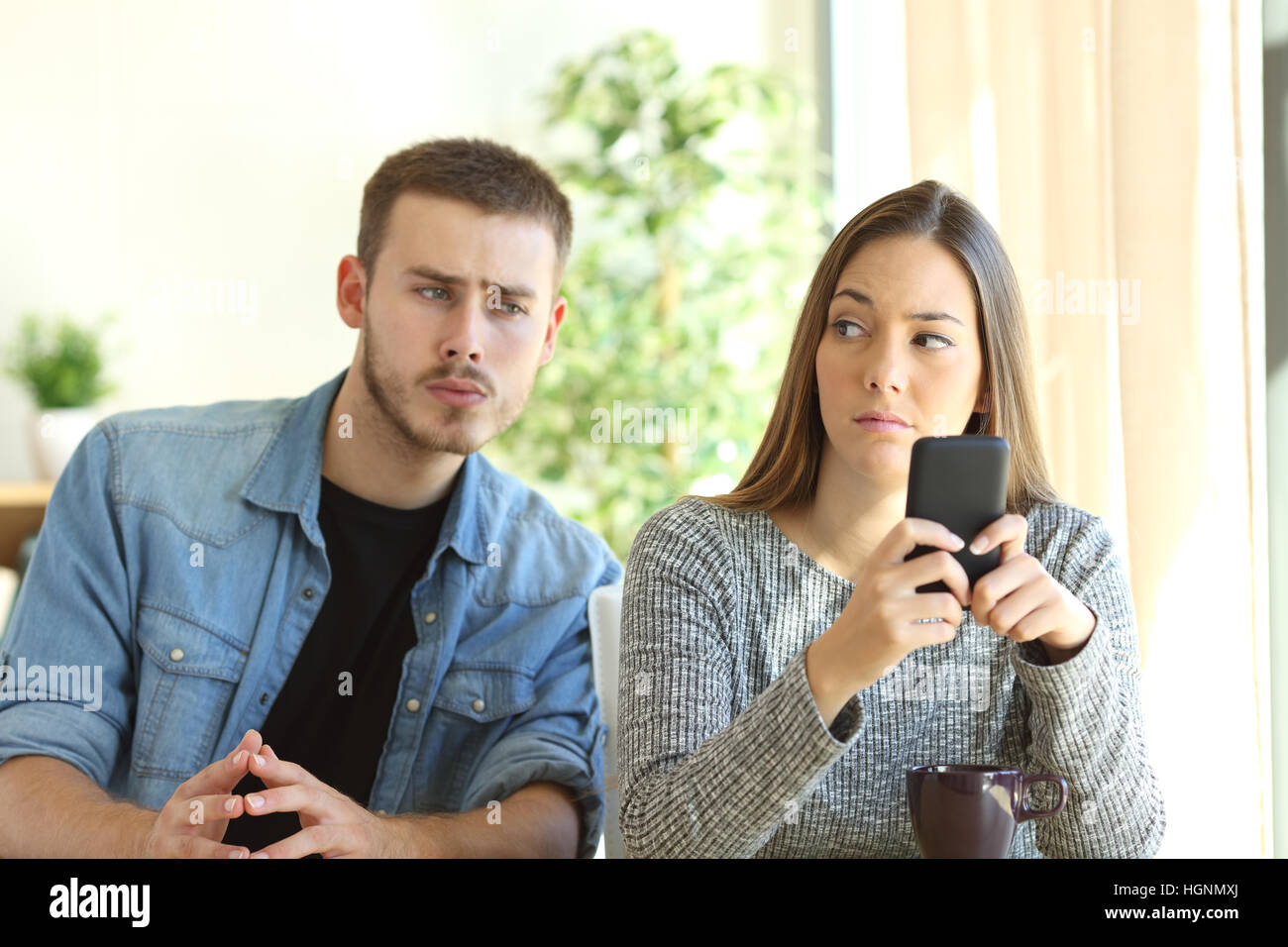 Jealous boyfriend spying his girlfriend watching her phone while she is looking him upset - Stock Image