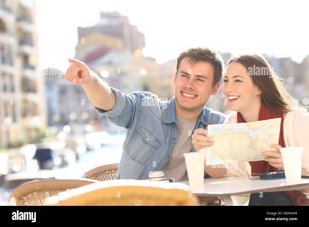 Couple of tourists searching location siting in an hotel terrace during a summer travel with a port in the background - Stock Image