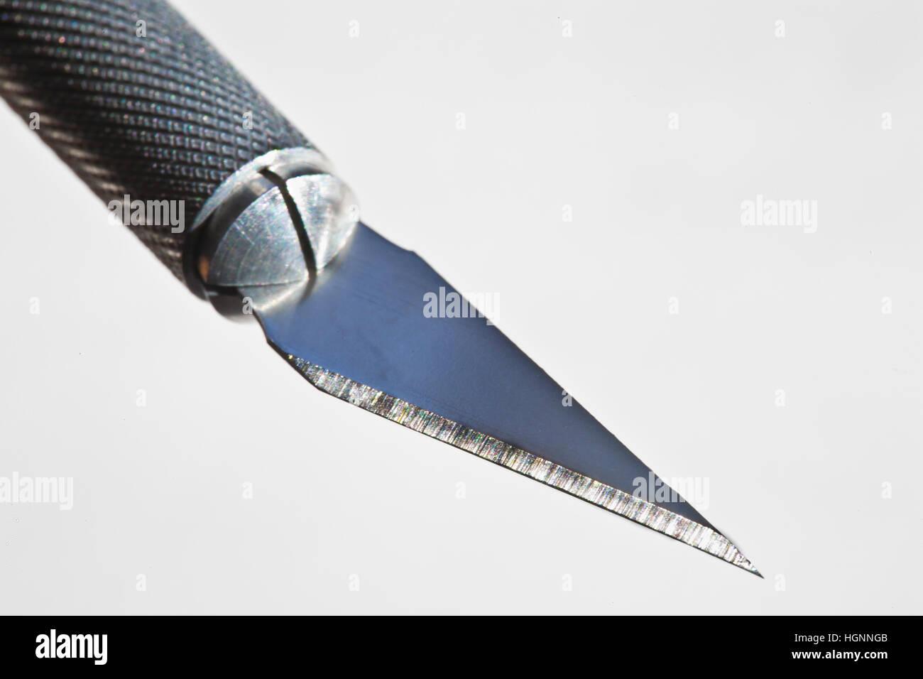 macro of xacto knife blade and handle on white backgrouond - Stock Image