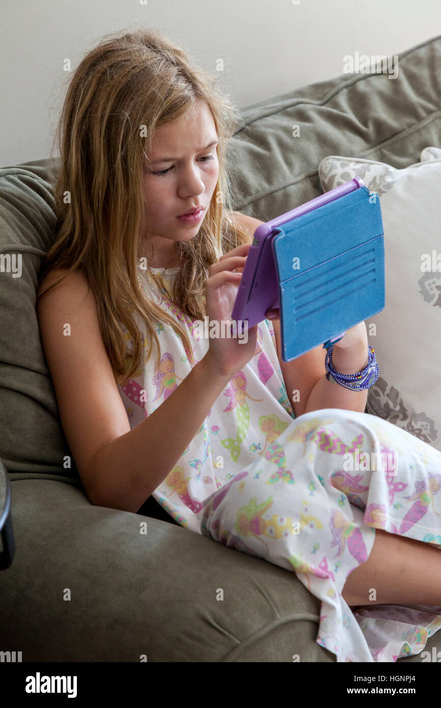 Eleven-year-old Girl Playing a game on iPad. - Stock Image