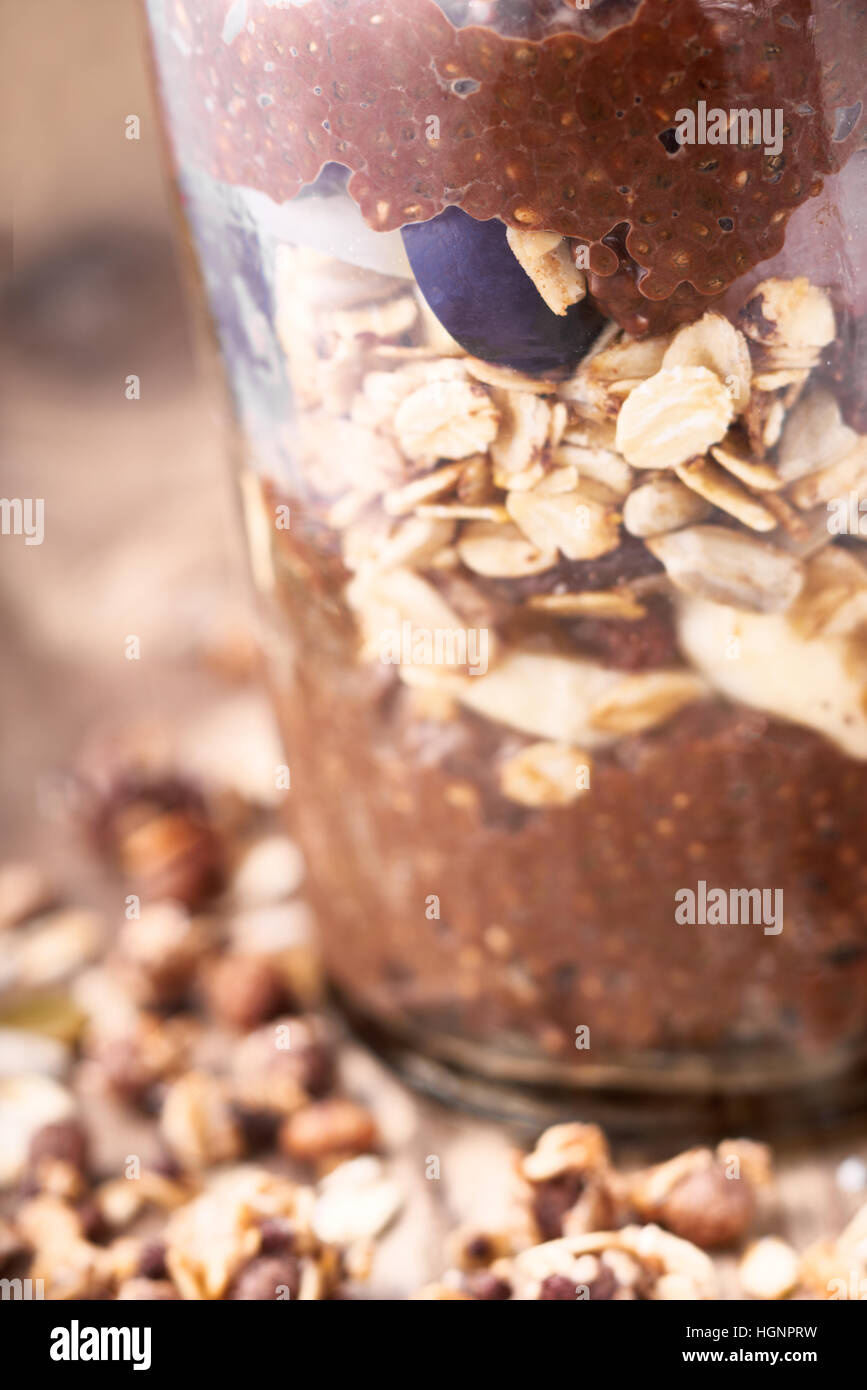 Chocolate chia pudding with oat flakes in the glass jar - Stock Image