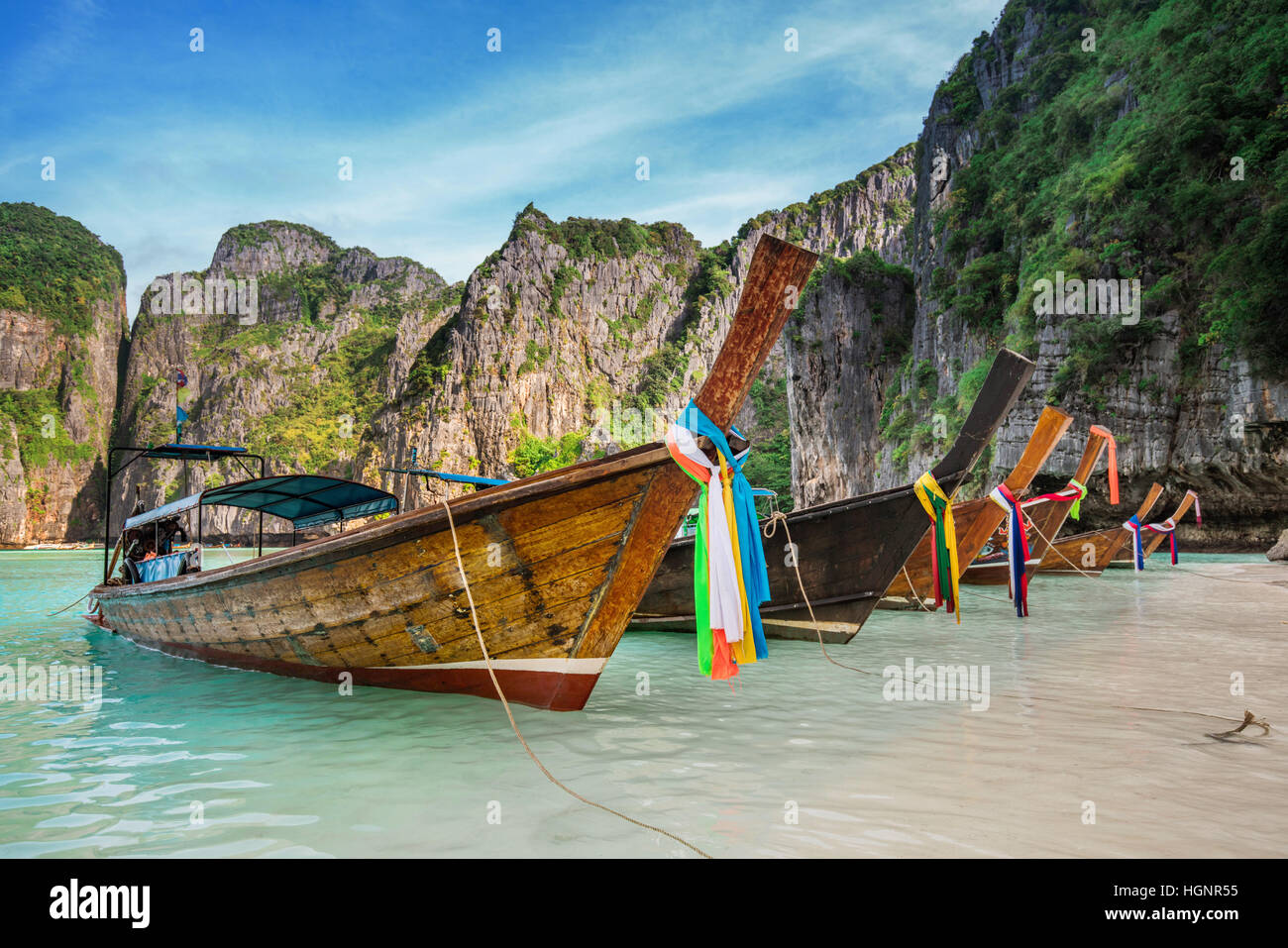 Thailand sea beach view round with steep limestone hills with many traditional longtail boats parking at Maya Bay, - Stock Image
