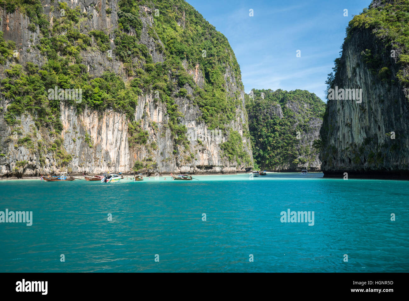 Jungle limestone cliffs around Phi-Phi Leh island with tourist boat parking - Stock Image