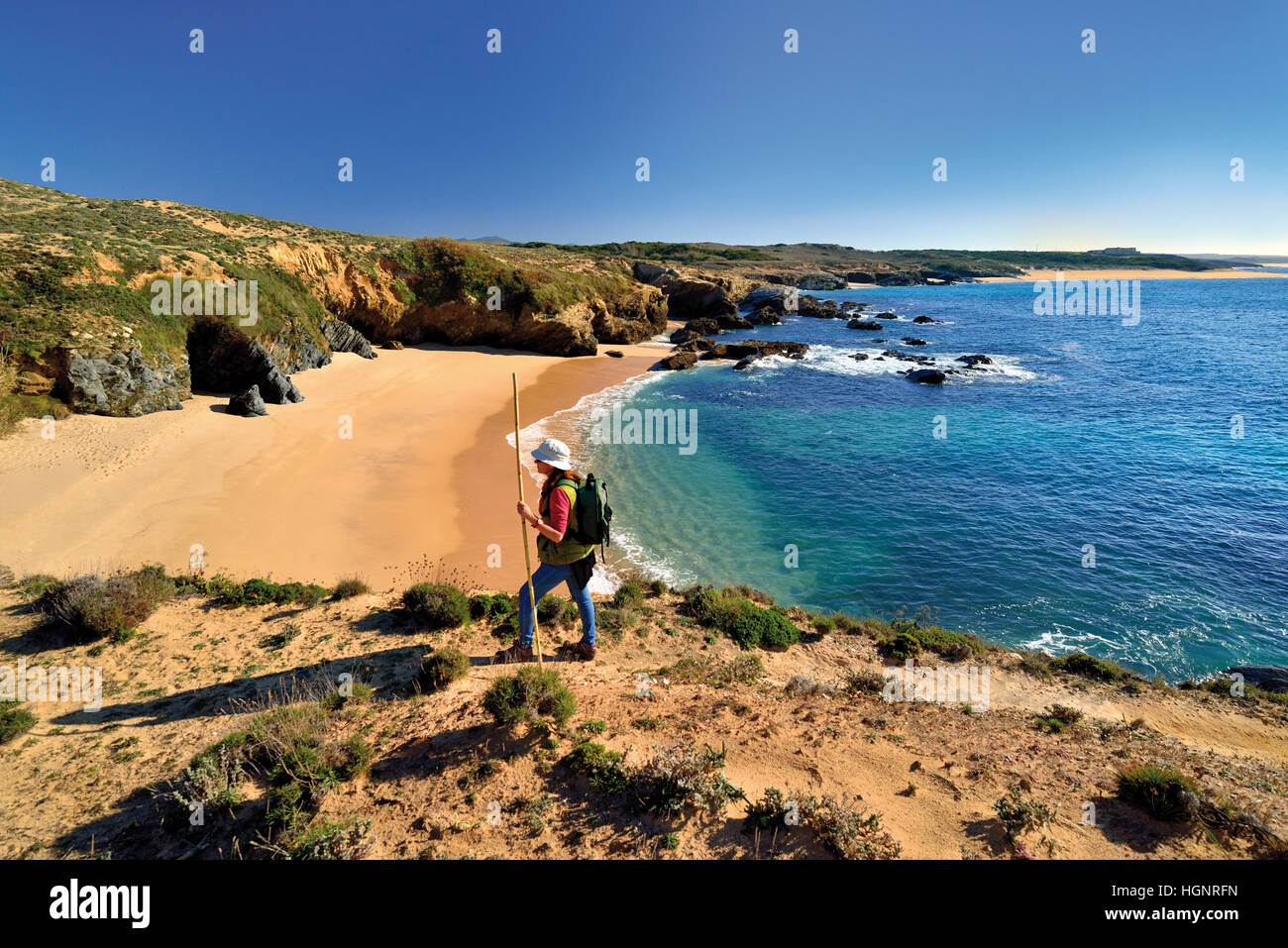 Woman with backpack and walking stick trekking along a sandy coastal trail along lonely beaches and a calm blue - Stock Image