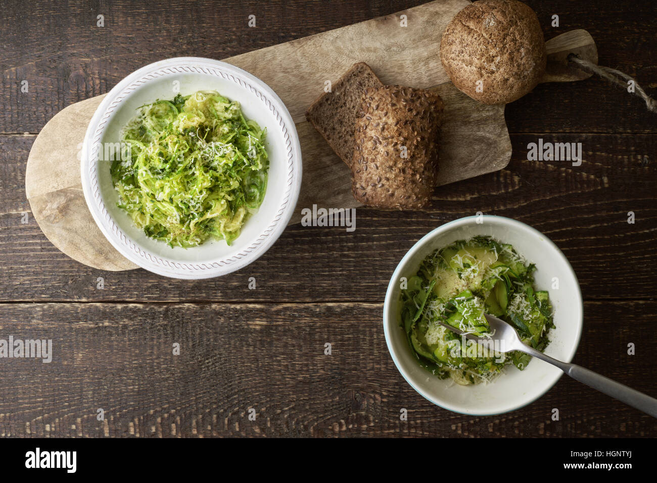 Zucchini noodles with cheese and bread on the wooden table top view - Stock Image