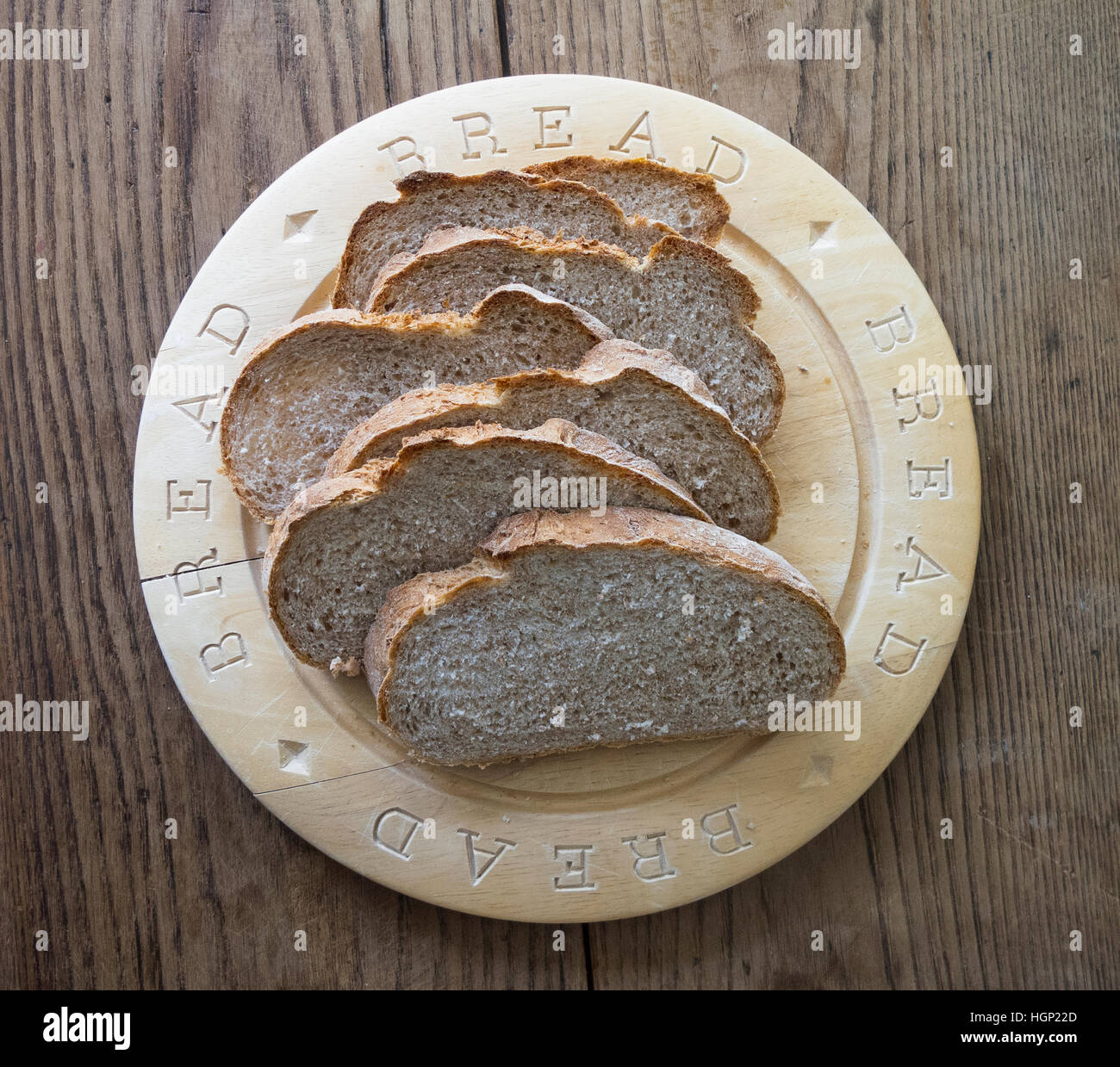 Sliced wholemeal brown bread on a wooden bread board on a wooden table - Stock Image