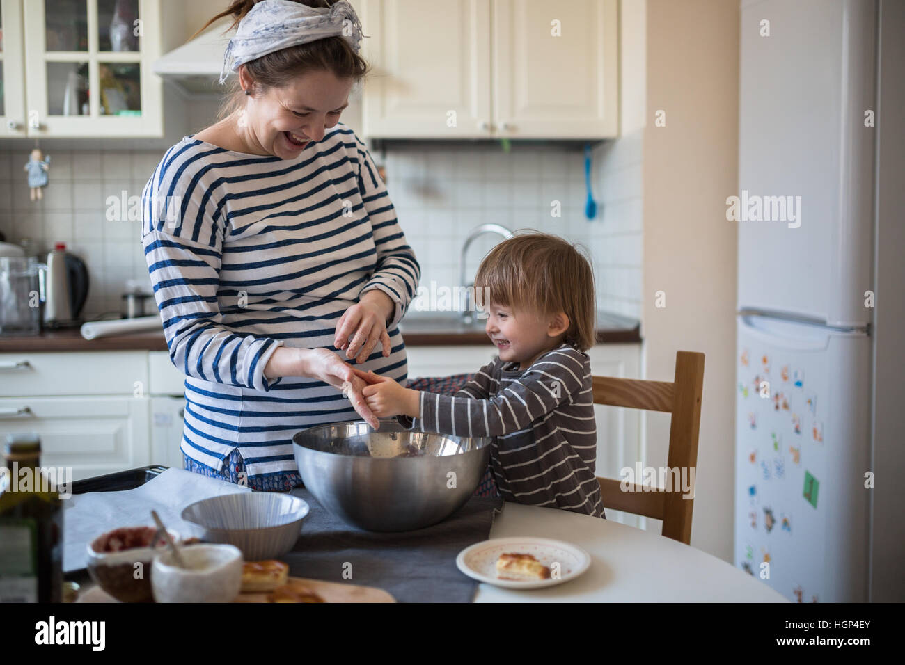 smiling young pregnant mother with dreadlocks is preparing in the kitchen with her son Toddler, dirty hands, make - Stock Image