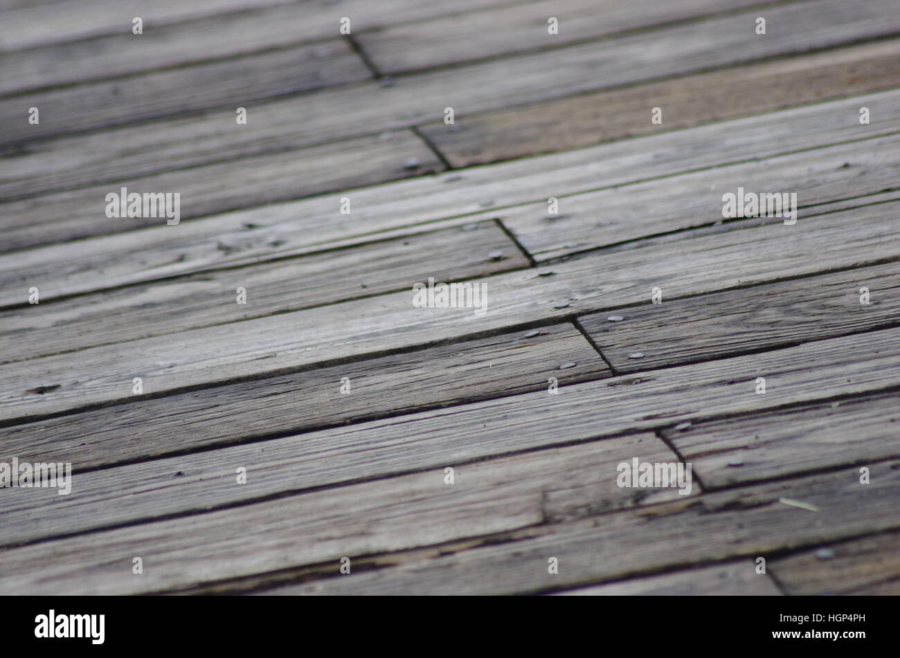 Brown and gray wooden boards with nails. Porch floor wood pattern chipped splintering holes cracks crooked diagonal Stock Photo