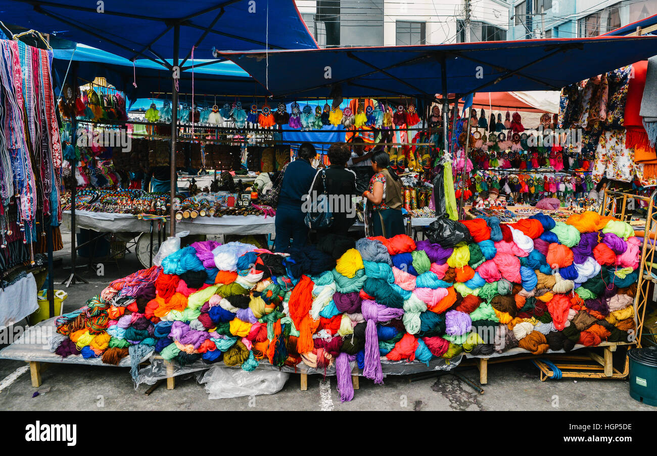 Traditional street market in Otovalo, Ecuador, full of textiles, fruit and vegetables, spices, jewerly and indigenous - Stock Image