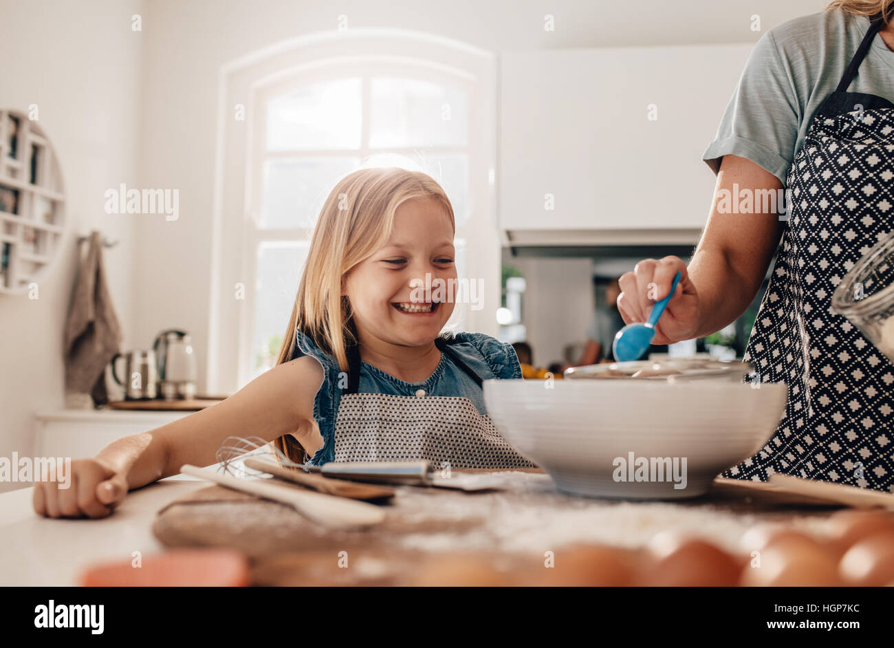 Happy little girl standing in kitchen and her mother cooking food. Mother and happy daughter baking in kitchen. - Stock Image