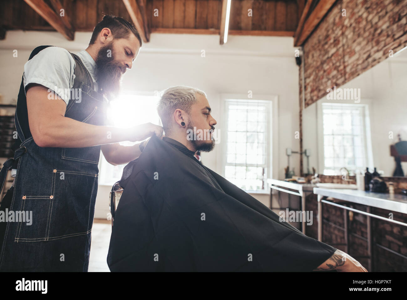 Side view shot of handsome young man getting haircut in salon. Hairstylist serving client in barber shop. - Stock Image