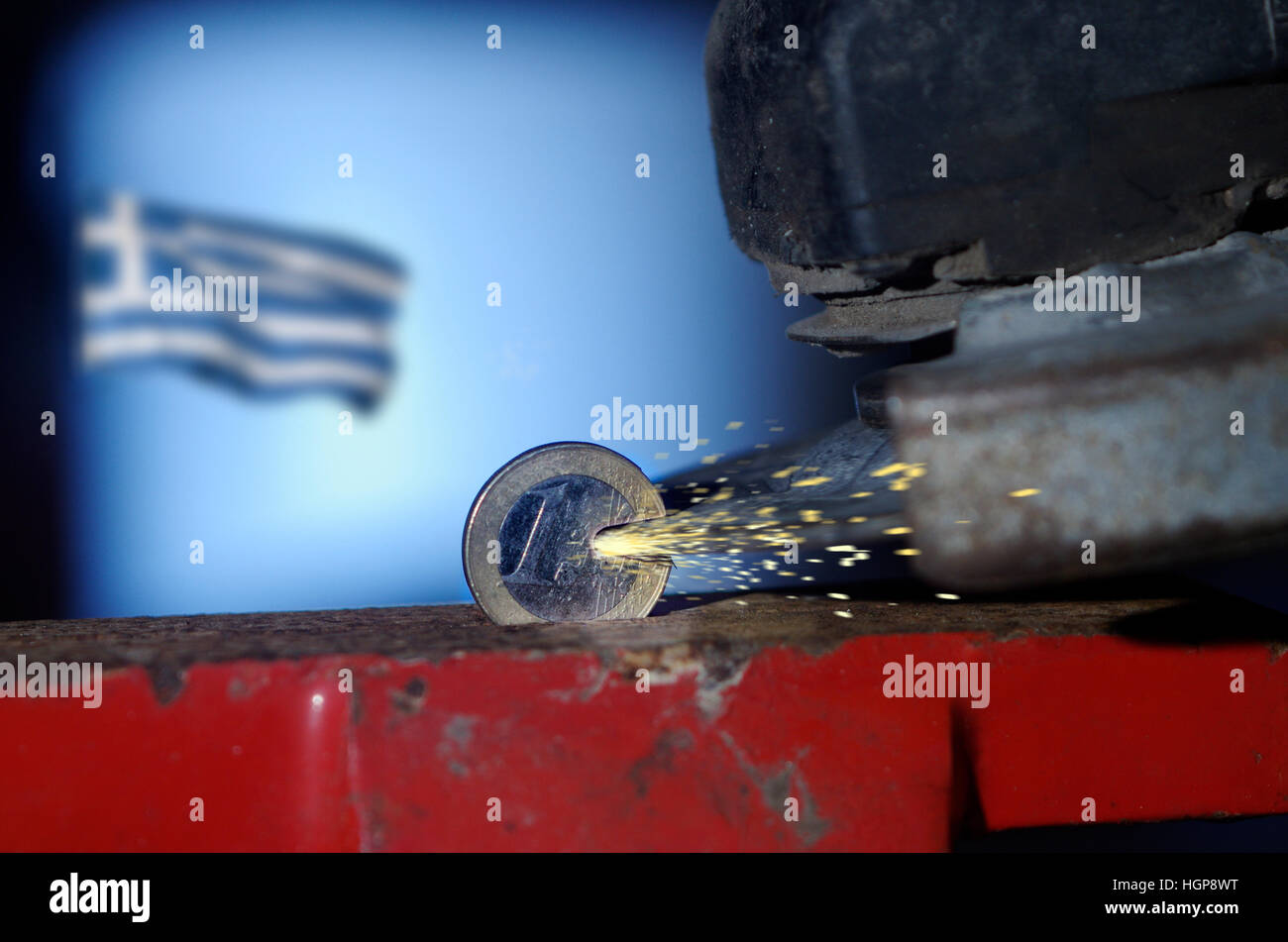 One Euro coin in a vice being cut with an angle grinder whilst Greek flag flies in background - Stock Image
