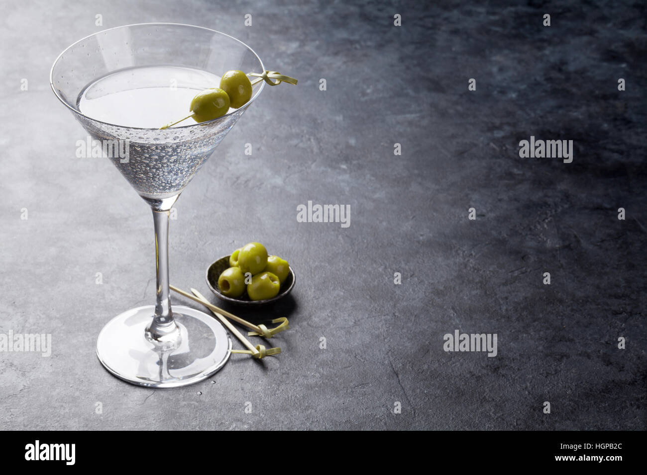 Martini cocktail on dark stone table. With space for your text - Stock Image
