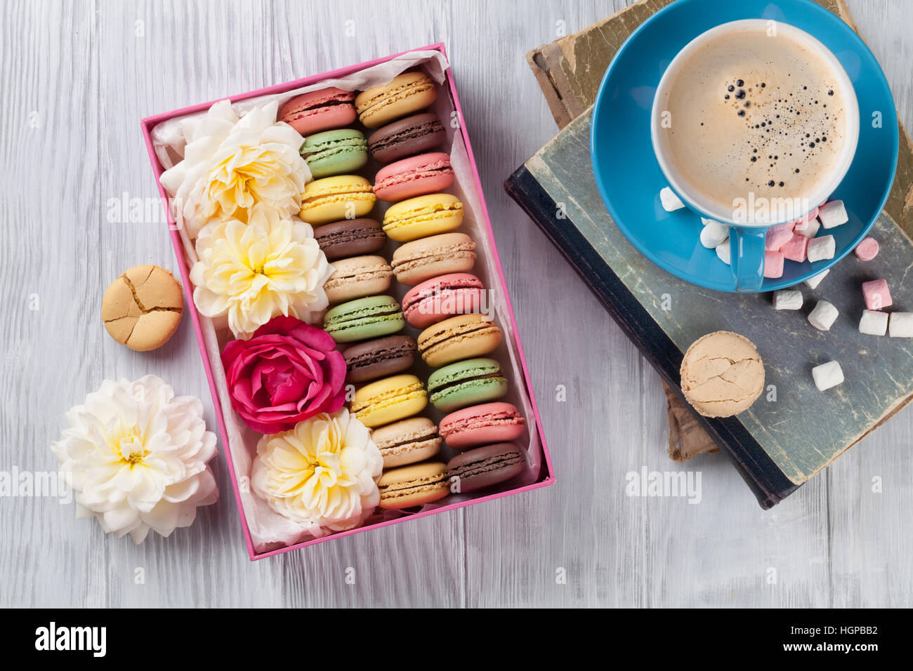 Colorful macaroons and coffee on wooden table. Sweet macarons in gift box and flowers. Top view Stock Photo