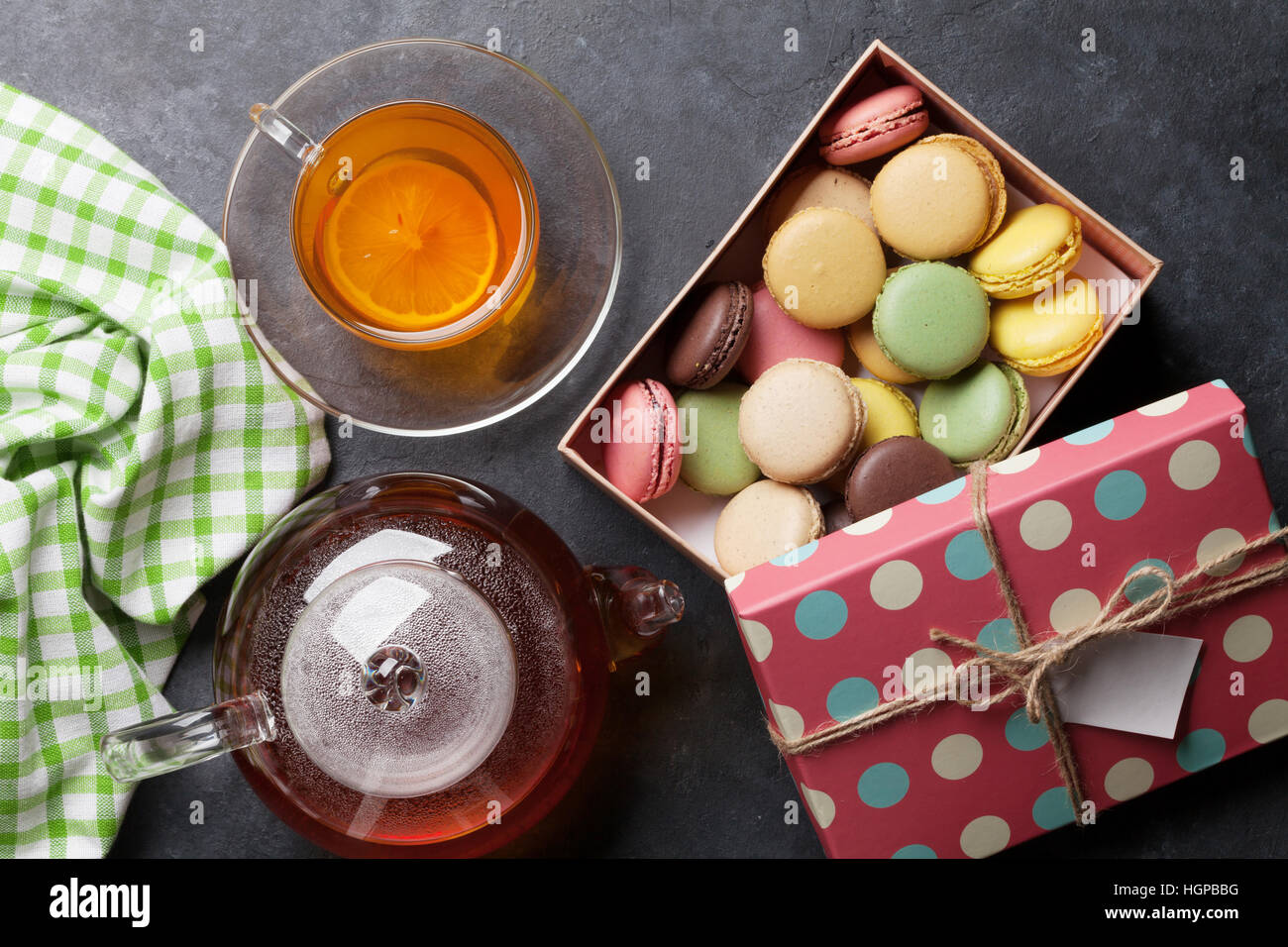Tea cup, teapot and macaroons gift box on stone table. Top view - Stock Image