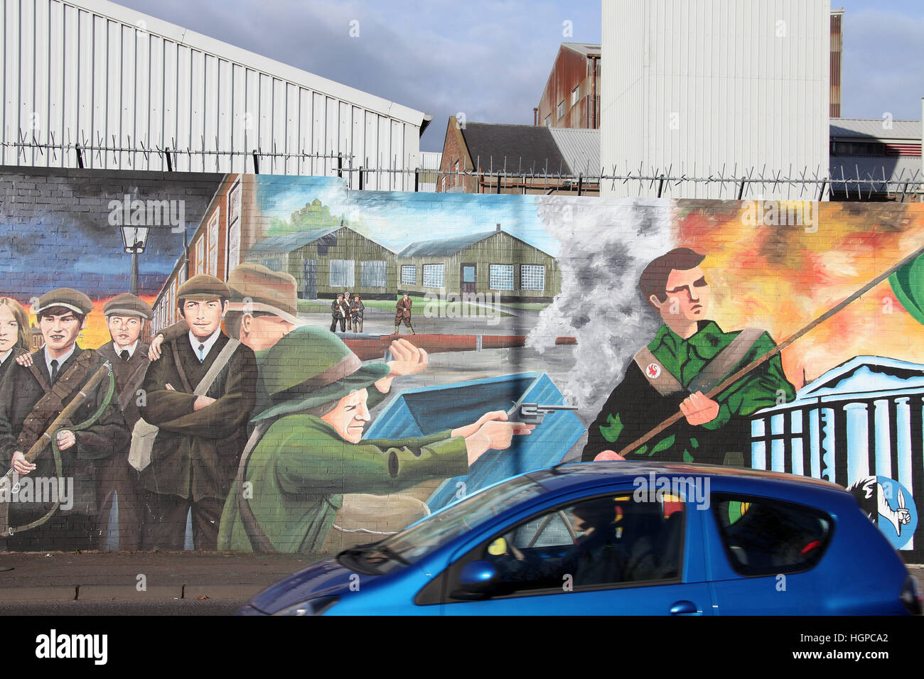 Car driving down the Falls Road in Belfast past the international Peace wall - Stock Image