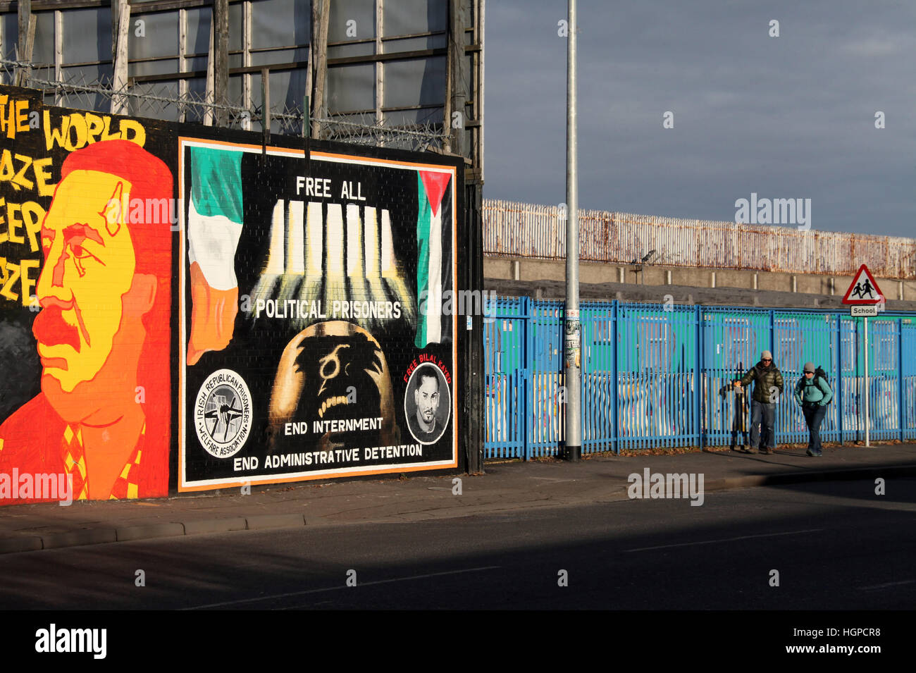 Tourists walking down the Falls Road in west Belfast past the International Peace Wall nurals - Stock Image