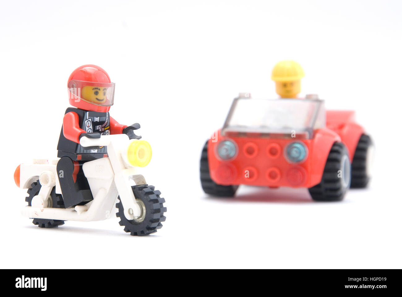 Mini figure Lego driving motorcycle and car - Stock Image