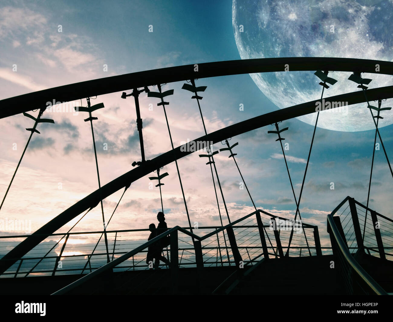 Fantasy landscape - silhouettes of two people walking a bridge with huge moon visible in the sky. Elements of this - Stock Image