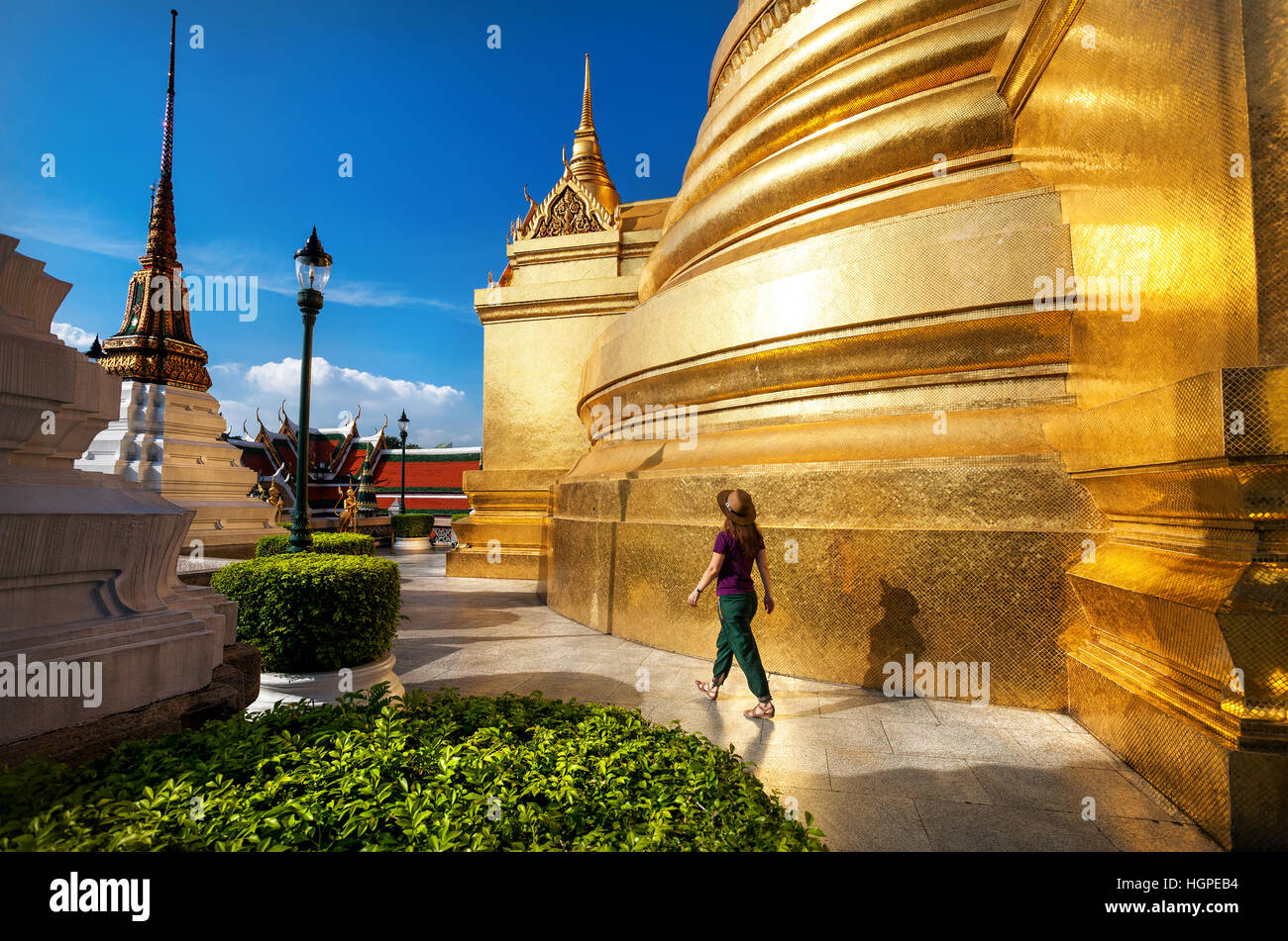 Woman tourist walking in the Temple of the Emerald Buddha with Golden Stupa in Bangkok at sunset - Stock Image
