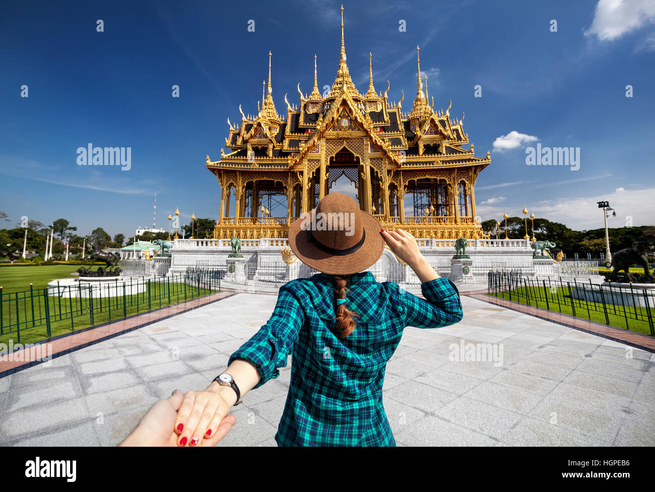 Woman in hat and green checked shirt leading man to the Ananta Samakhom Throne Hall in Thai Royal Dusit Palace, - Stock Image