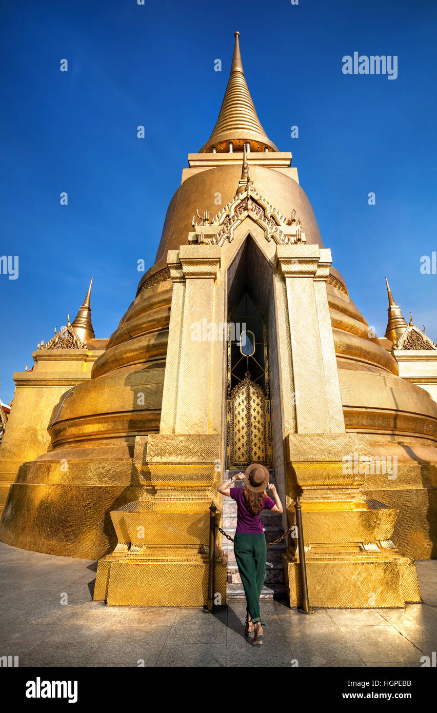 Woman tourist walking in the Temple of the Emerald Buddha near big Golden Stupa in Bangkok at sunset - Stock Image