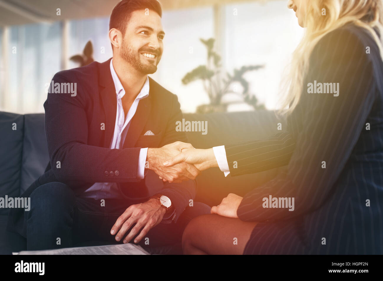 Businessman handshake with businesswoman in sunset at office - Stock Image