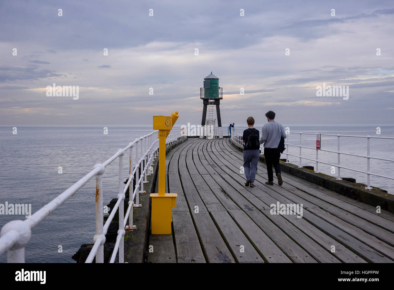 With a calm sea and blue sky, a couple stroll along the West Pier extension on a summer's evening - Whitby, - Stock Image