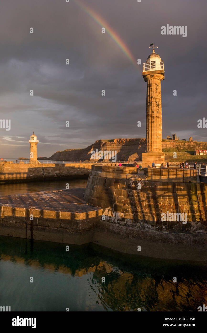 Rainbow and dark sky over sunlit lighthouses and harbour entrance, Abbey on the cliffs beyond - Whitby, North Yorkshire, - Stock Image