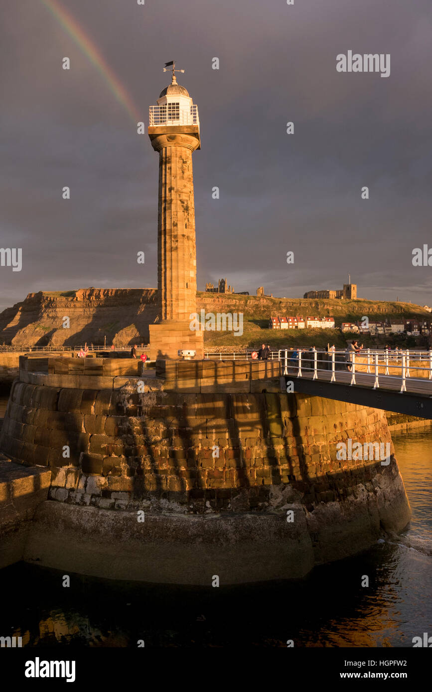Rainbow and dark sky over sunlit lighthouse, harbour entrance, Abbey and St. Mary's Church - Whitby, North Yorkshire, - Stock Image