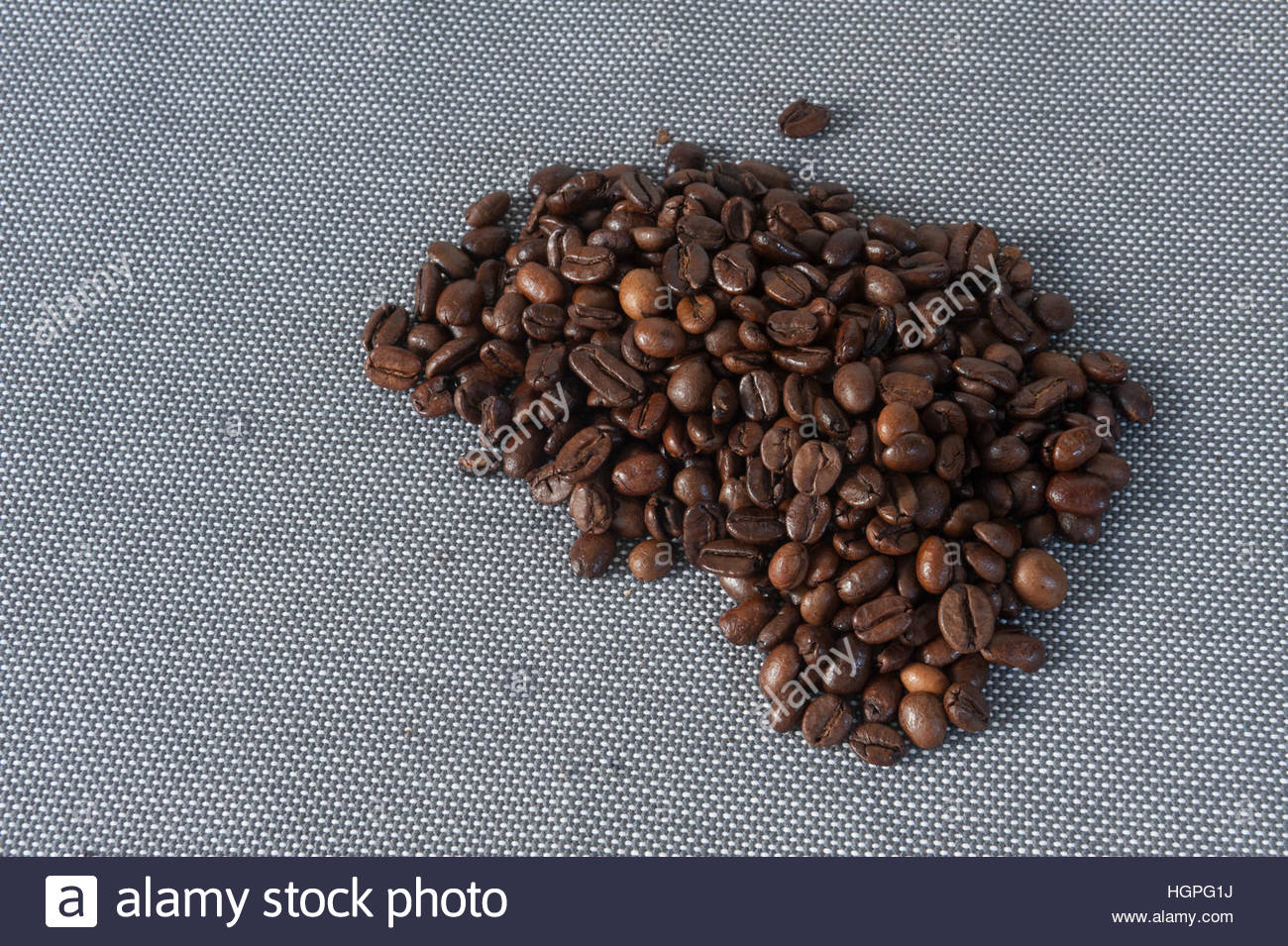 Coffee beans pile on a blue table mat - Stock Image