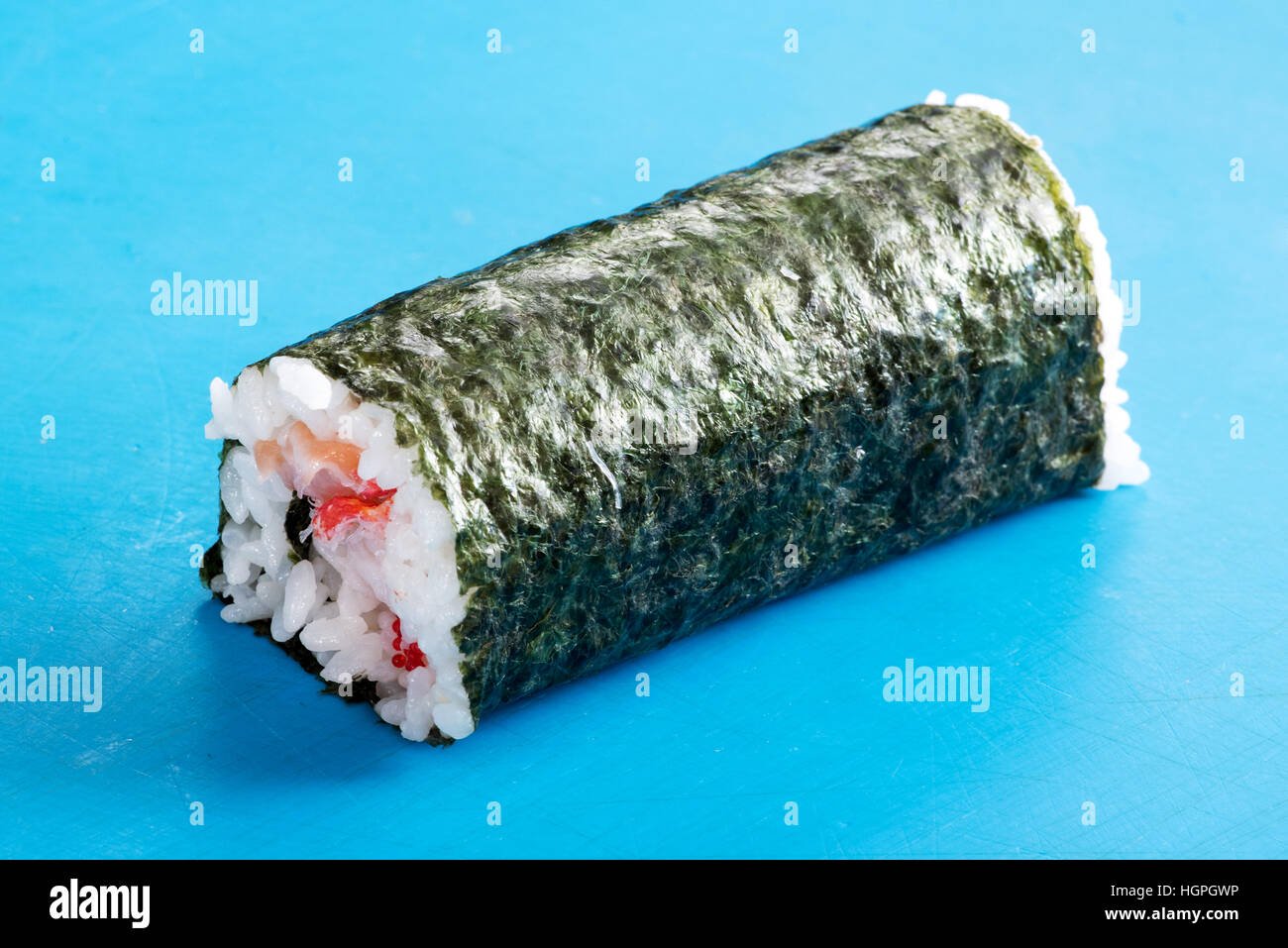 Close up of uncut Futomaki sushi roll in nori on blue surface - Stock Image