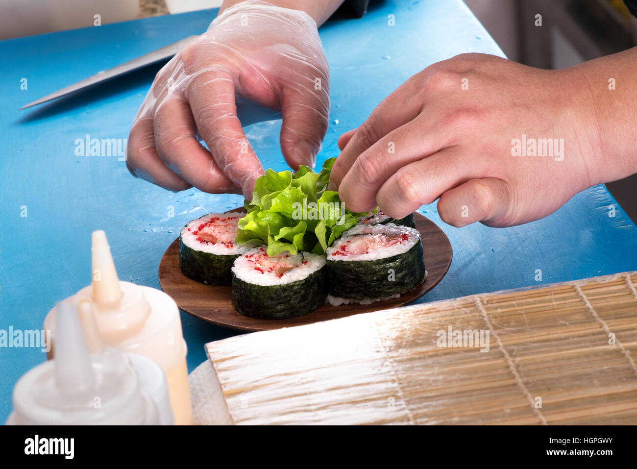 Close up view of chefs hands carefully placing Futomaki rolls on wooden plate - Stock Image