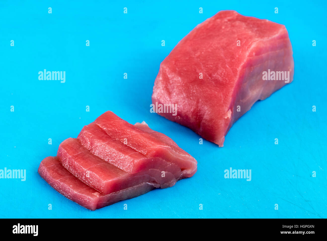 Sliced fresh raw tuna fillet or steak for use in Japanese sushi and sashimi arranged diagonally on a blue background - Stock Image
