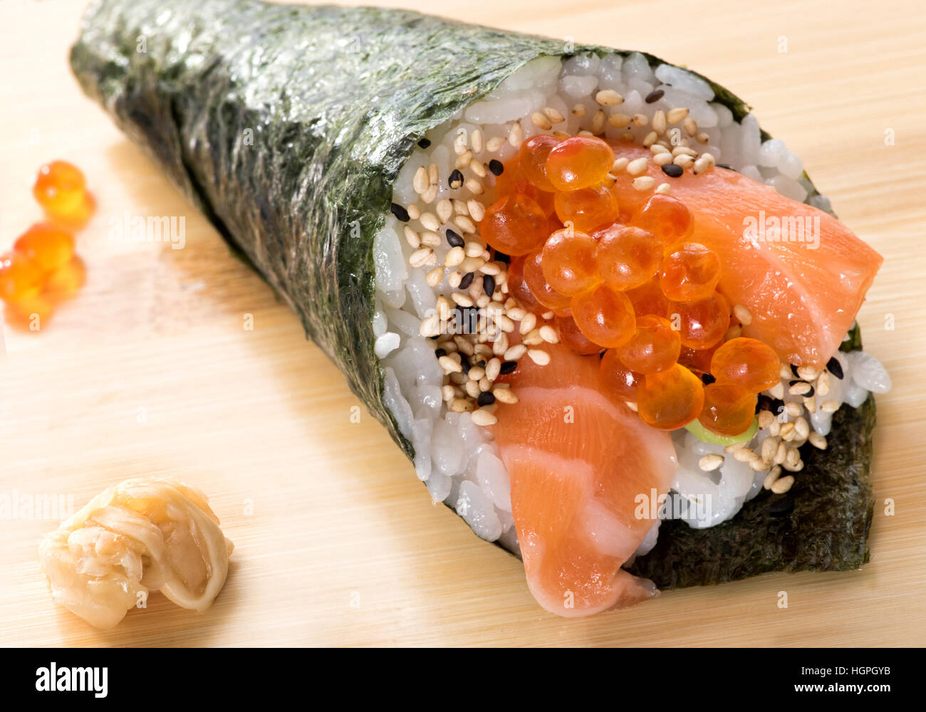 Close view of Japanese cuisine sushi roll with salmon, caviar and sesame served on wooden board - Stock Image