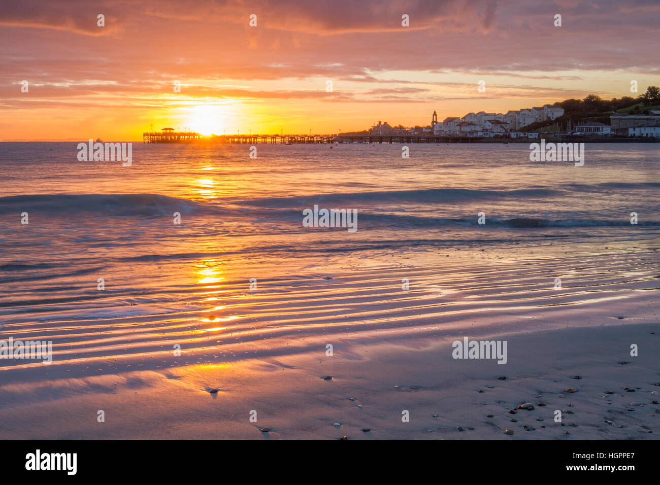 Beautiful Sun Rising Over Silhouette Pier And Waves On Beach Stock