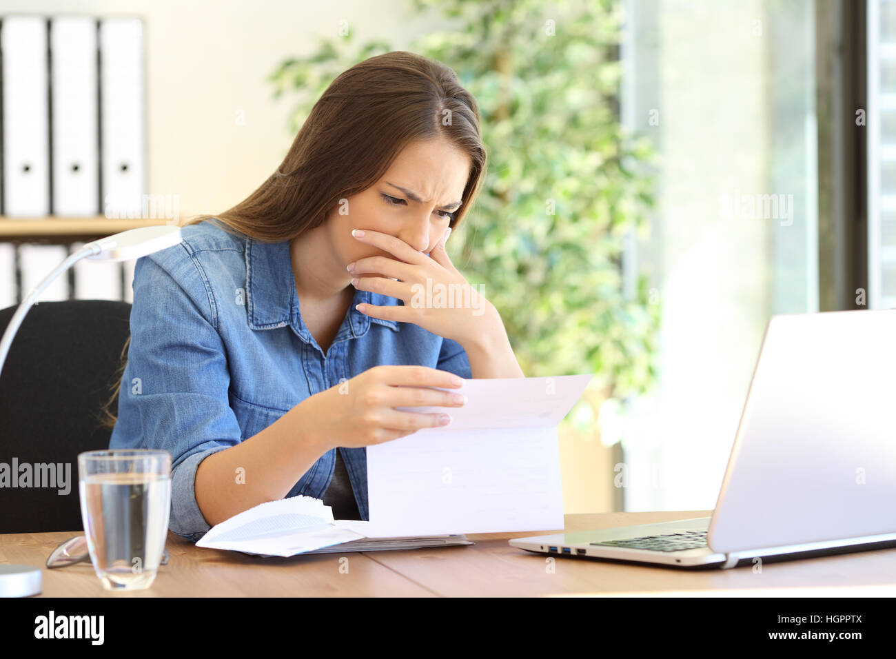 Worried entrepreneur girl working at office reading bad news in a letter on a desktop - Stock Image