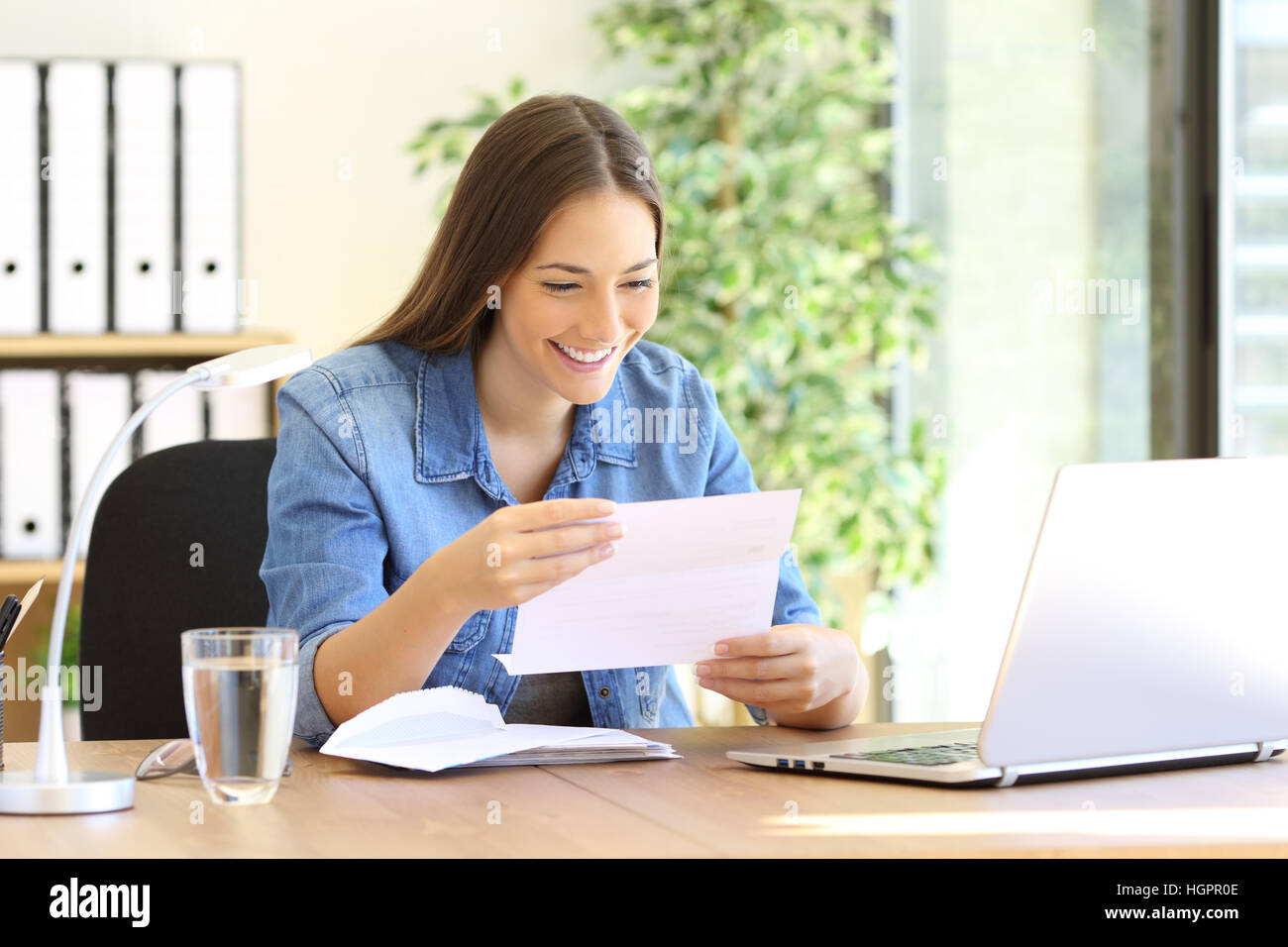 Happy entrepreneur woman reading good news in a letter in a desk at office - Stock Image