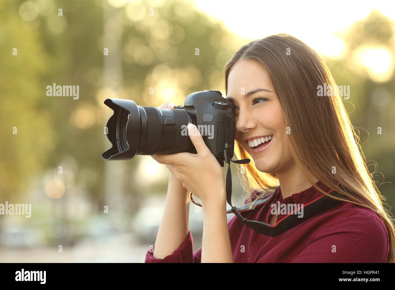 Photographer photographing with a digital camera outdoors at sunset with a warm light - Stock Image