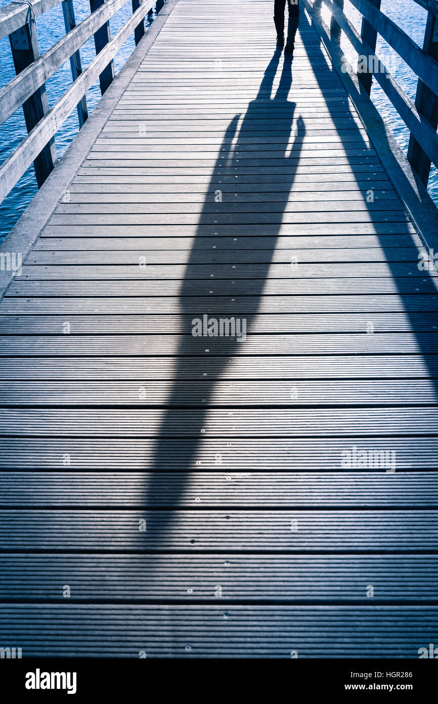 Whole body shadow silhouette of female person seen with the shoes walking at planks of wooden pier above the sea - Stock Image